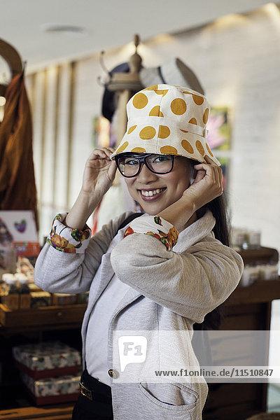Junge Frau beim Anprobieren des Hutes im Geschäft  Porträt