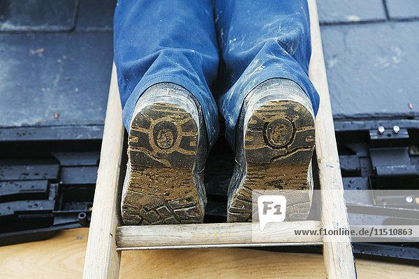 Ein Mann steht auf einer Leiter in Dachhöhe  die Füße in Arbeitsstiefeln.