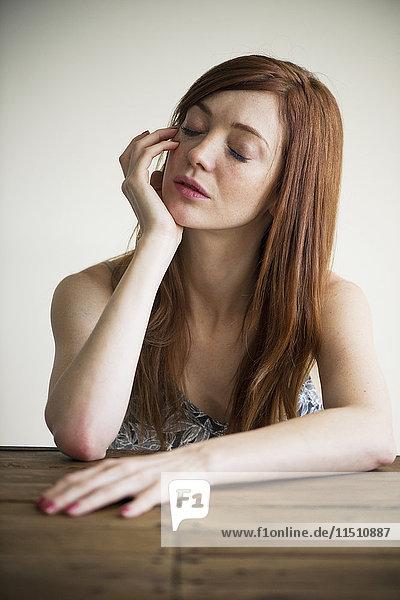 Frau hält Kopf mit geschlossenen Augen