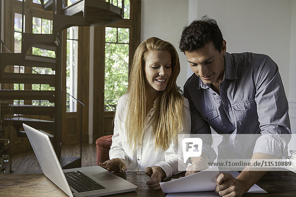 Couple using laptop computer together in home office