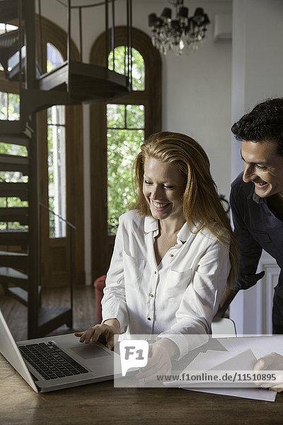 Paare  die zu Hause am Laptop arbeiten.