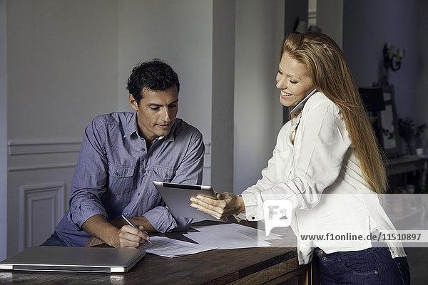 Frau spricht am Handy und zeigt Ehemann digitales Tablett