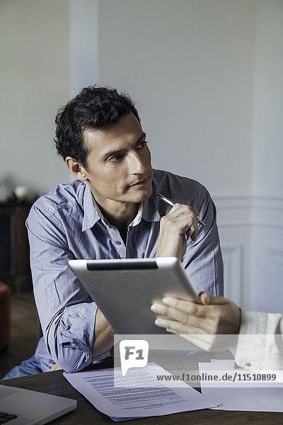 Der Mann  der als Kollege zuhört  zeigt ihm etwas auf einem digitalen Tablett.