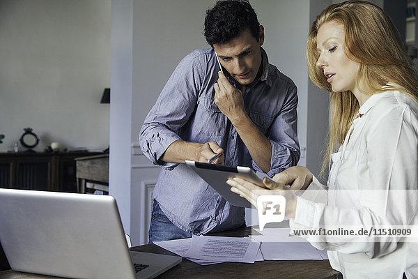 Paar  das zu Hause Geschäfte mit dem Handy und dem digitalen Tablett macht.