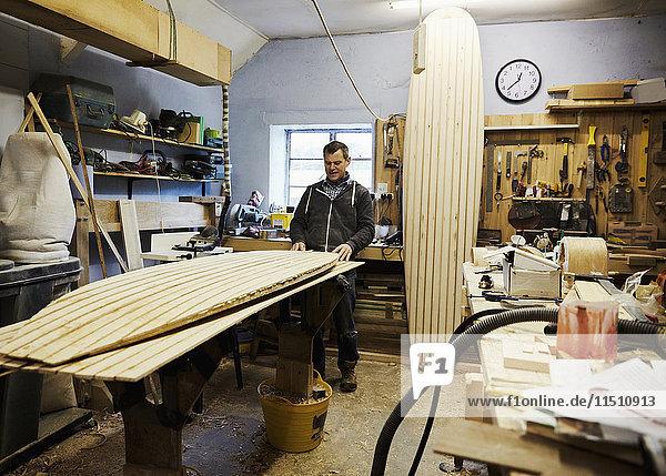 Ein Surfbrett-Workshop  ein langes  aufrecht stehendes Brett und ein Brett in Produktion auf einer Werkbank. Ein Surfbrettmacher bei der Arbeit.