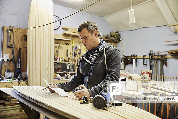 Mann steht in einer Werkstatt mit einem hölzernen Surfbrett  hält Papier und Stift.