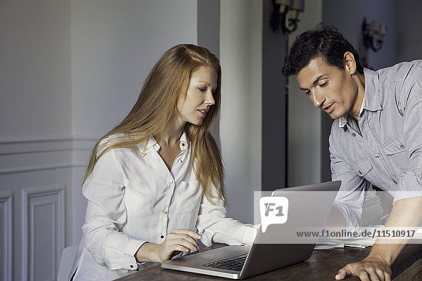 Couple using laptop computer at home