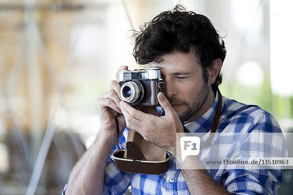 Mann fotografiert mit einer Filmkamera