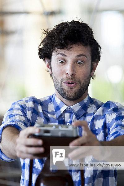 Ein Mann  der ein lustiges Gesicht macht  während er einen Selfie nimmt.