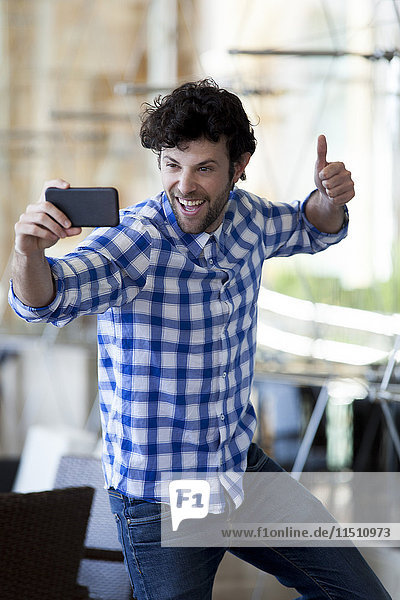 Ein Mann  der einen Daumen hochzieht und einen Selfie mit seinem Smartphone nimmt.