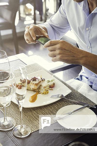 Mann  der sein Essen im Restaurant mit dem Smartphone fotografiert.