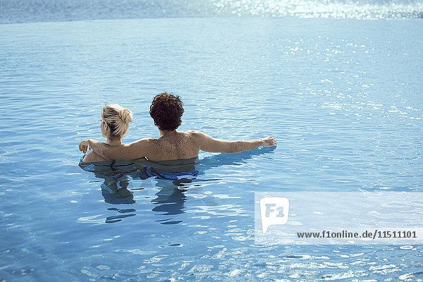 Paar entspannt zusammen im Wasser  Rückansicht