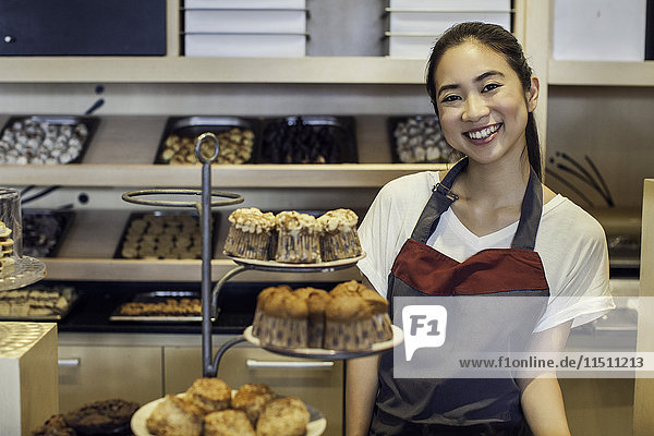 Frau lächelt hinter Bäckerei-Theke  Portrait