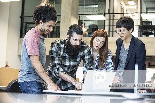 Kreative Kollegen  die gemeinsam am Laptop arbeiten