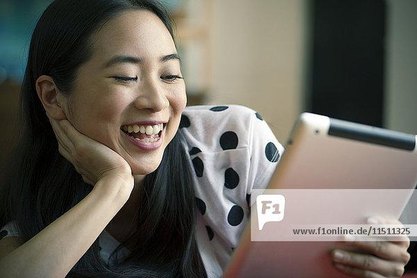 Junge Frau sieht sich einen Film auf einem digitalen Tablett an