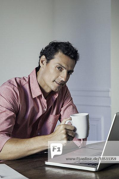 Mann entspannt mit Laptop und Tasse Kaffee