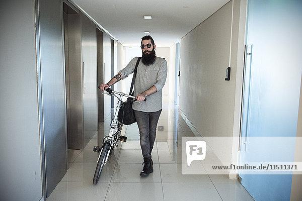 Mann geht mit dem Fahrrad durch den Flur