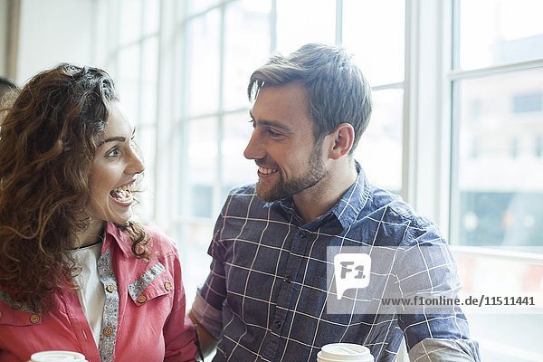 Ein fröhliches Paar  das sich im Café unterhält