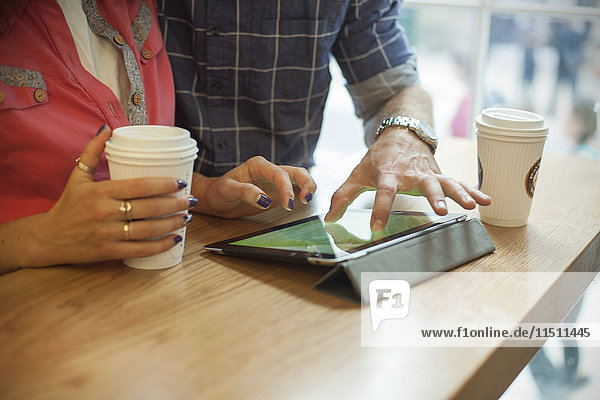 Paar mit digitalem Tablett im Coffee Shop  beschnitten