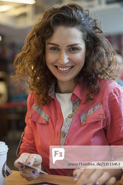 Frau bezahlt mit Kreditkarte  Portrait