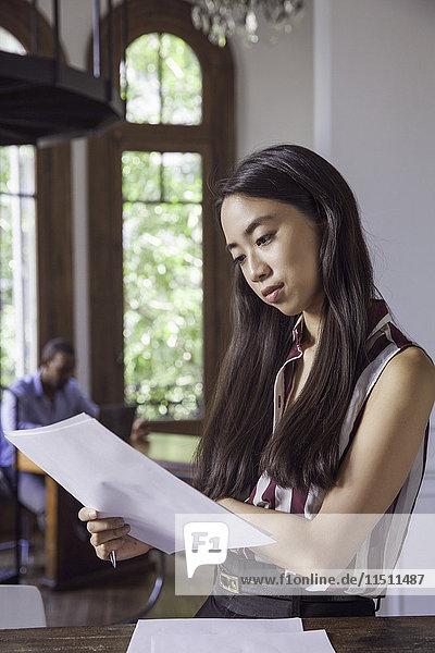 Frau liest Dokument im Büro