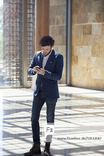 Man Text-Messaging während des Spaziergangs durch die Lobby