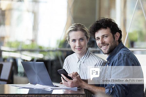 Paar arbeitet an ihren Verlobten mit Laptop und Smartphone