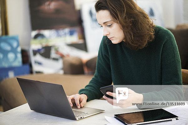Multi-Tasking für Frauen mit Hilfe von Laptop  digitalem Tablett und Smartphone