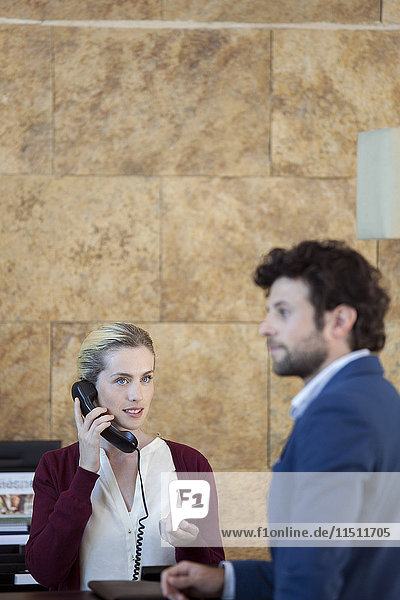 Receptionist verifying customer's credit card on the phone