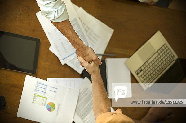 Geschäftsfreunde schütteln sich während des Meetings die Hand