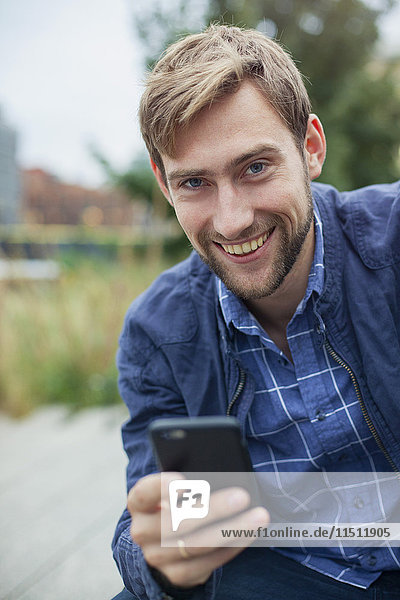 Man using smartphone outdoors  smiling  portrait