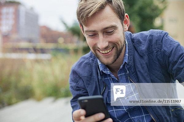 Man text messaging outdoors