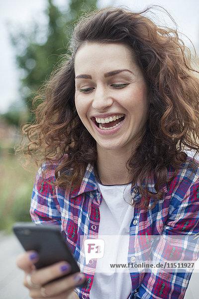 Junge Frau lacht  während Textnachrichten im Freien gesendet werden