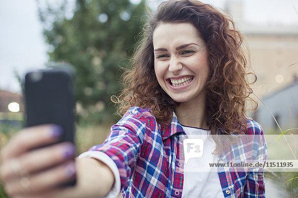 Junge Frau mit einem Selfie im Freien