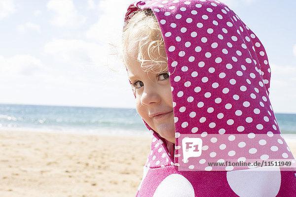 Mädchen in Kapuze mit Punkten am Strand