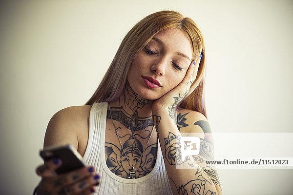 Tätowierte Frau mit Smartphone
