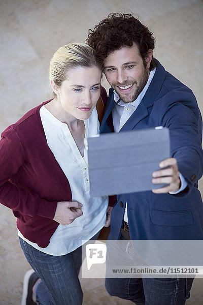 Pärchen mit digitalem Tablett zur Aufnahme eines Selfies