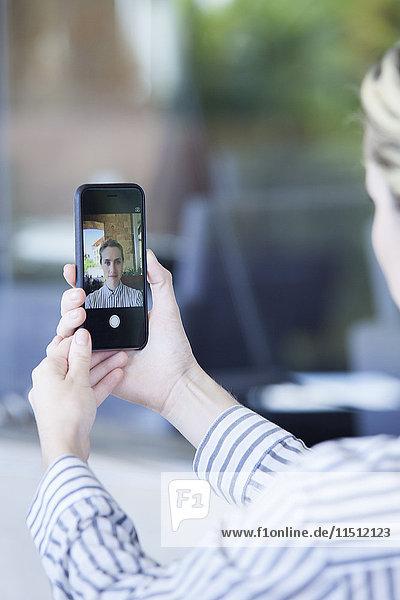 Frau  die ein Smartphone benutzt  um einen Selfie zu nehmen.