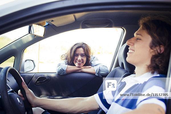 Frau schaut in das Autofenster  während der Mann auf dem Fahrersitz sitzt.