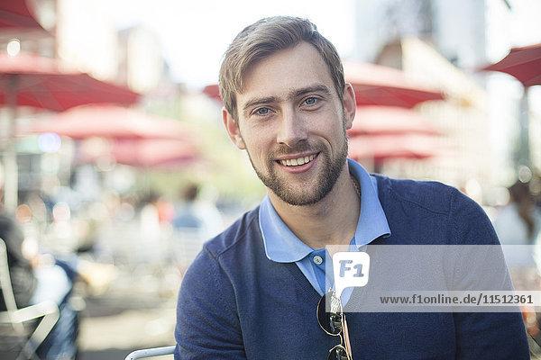 Junger Mann lächelt im Freien  Porträt