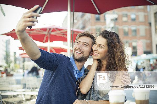 Pärchen posieren für einen Selfie im Outdoor-Café