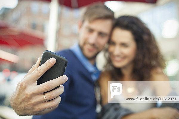 Mann fotografiert sich mit seiner Frau auf dem Smartphone