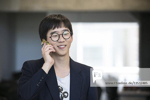 Mann  der sein Handy benutzt  lächelt fröhlich.