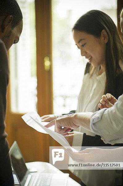 Büroangestellte diskutieren über Dokumente