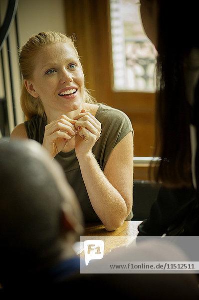 Frau im Gespräch mit Kollegen im Büro