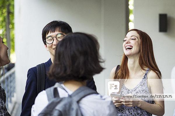 Junge erwachsene Freunde  die rumhängen und lachen.