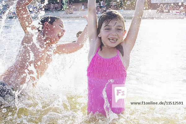 Geschwister spielen im Wasser