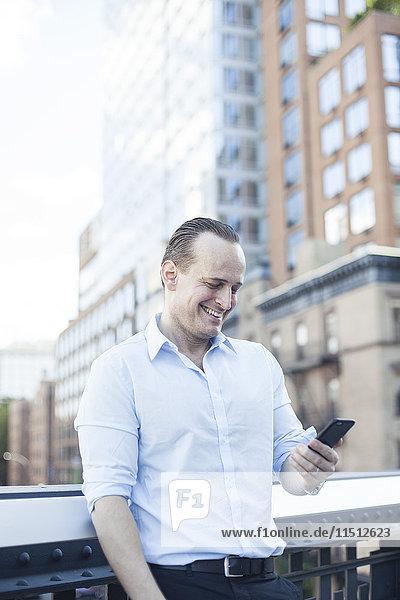 Mann lacht  während er sein Smartphone im Freien benutzt.