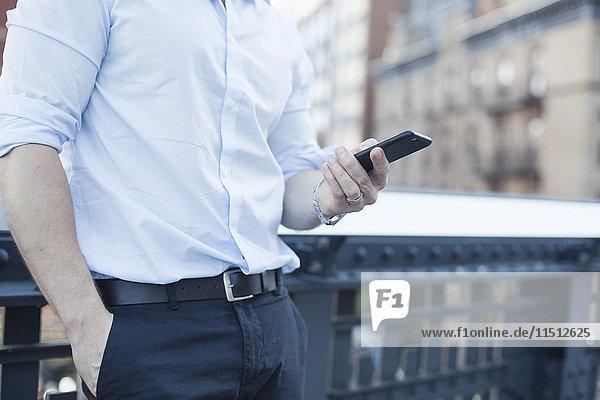 Geschäftsmann mit Smartphone  Mittelteil