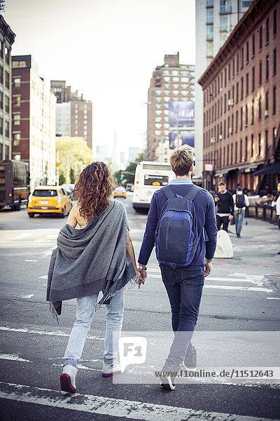 Paar überqueren Stadtstraße zusammen  Rückansicht